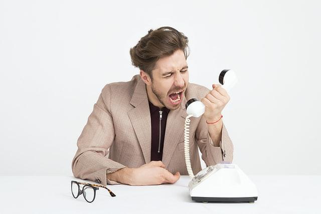 男が電話越しに怒鳴ってる